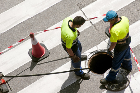 full of holes: utilities workers moves the manhole cover to check the sewer line for clogs