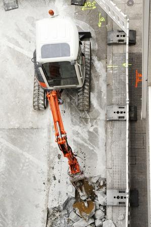 mine site: large jackhammer construction machine destroying pavement of a city street