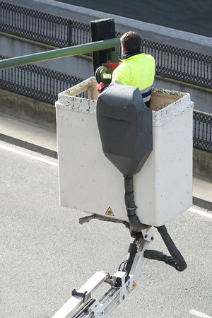 linemen: electrician worker repairs traffic lights from elevator bucket truck in the city