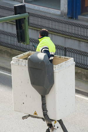 heights job: electrician worker repairs traffic lights from elevator bucket truck in the city