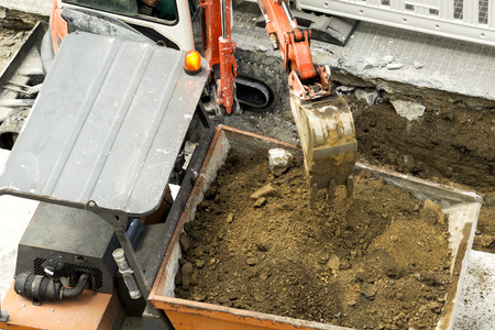dumper truck: excavator  carrying debris into a construction  dumper  truck , chimpin, in city street Stock Photo