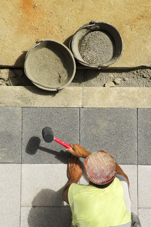mine site: mason construction worker placing tiles on the sidewalk  in the city street Stock Photo
