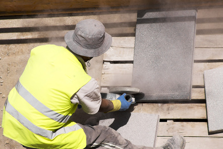 mine site: mason construction  worker cutting tiles with electric grinder for repairing sidewalks