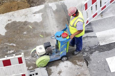 presslufthammer: Maurer Bauarbeiter in Stadtstra�e mit Schneiden Pflaster Maschine und gro�en Bohrhammer Lizenzfreie Bilder