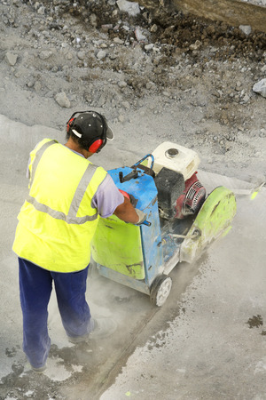 mine site: construction worker using cutting  pavement machine in the city street