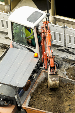mine site: excavator  carrying debris into a construction  dumper  truck , chimpin, in city street Stock Photo