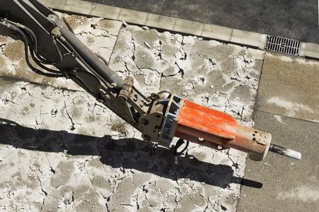 mine site: large jackhammer construction machine destroying pavement of a city street  close up