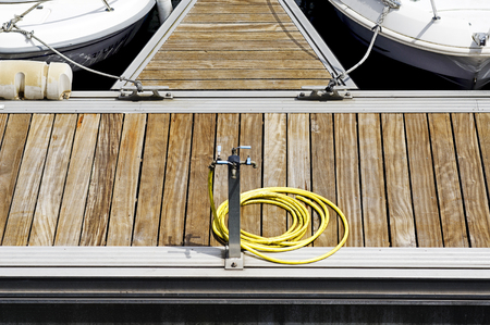 wather: wather hose in wooden dock pier marina  with boats
