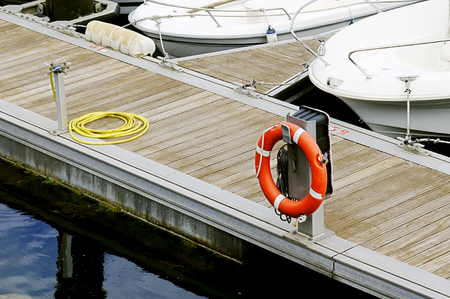 wooden dock: wooden dock pier marina  with boats, water hose and  ring buoy