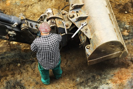 excavator: construction worker works repairing the sewer and wather  pipes in the street city