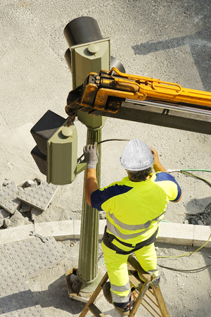 heights job: electrician worker of utility company to repair traffic lights in the street city Stock Photo