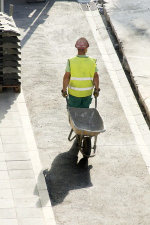 construction vibroroller: mason construction worker with  wheelbarrow  to repair road in the street city