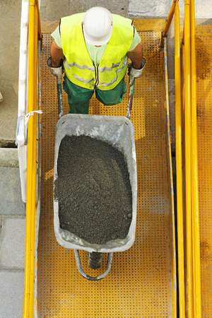 construction vibroroller: mason construction worker to load cement in the wheelbarrow  to repair road in the street city