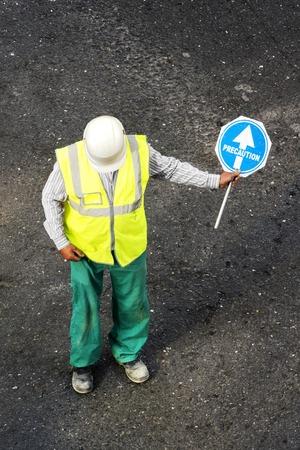 precaution: construction mason worker with precaution in road signal street of city