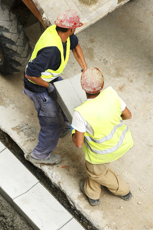 construction vibroroller: two mason construction workers carrying a tile to repair sidewalks in the street city