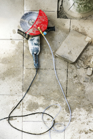 vibrating: electric grinder with tiles slabs to repair  sidewalks for  construction mason  worker in the street city