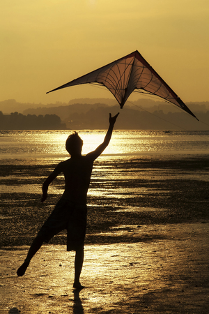 man flying: young man flying a kite