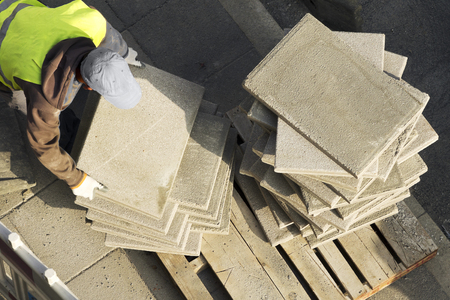 vibrating: construction mason worker to repair tiles in the sidewalk slabs at road in the city street