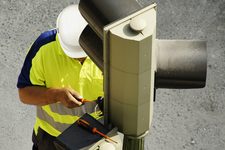 heights job: worker of utility company electrician to repair traffic lights in the city street