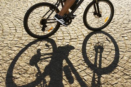 athletic wear: shadow of  cyclist flowing by cobblestone street