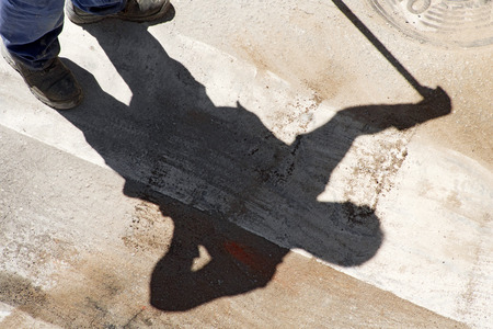 vibrating: mason construction worker with a brush shadow in the street city