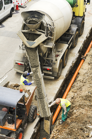 concrete truck: construction worker with concrete truck to repair water and sewer pipes in the city street