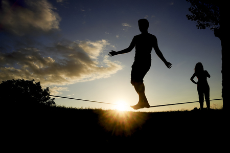 slack: man balancing in slack line , slacklining , and woman looks at him  at sunset Stock Photo