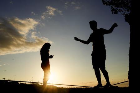 slack: man balancing in slack line , slacklining , and woman looking  mobile phone at sunset
