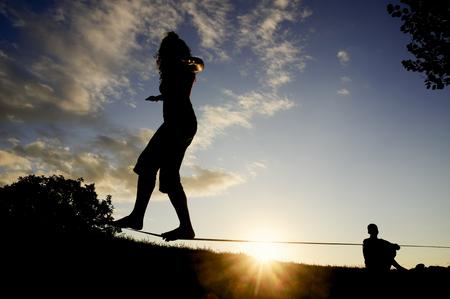 slack: woman balancing in slack line , slacklining , and man looks at him  at sunset