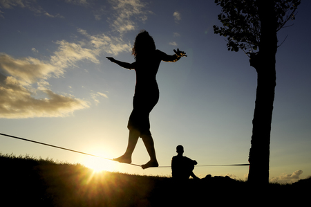 slack: woman balancing in slack line , slacklining , and man looks at him  at sunset