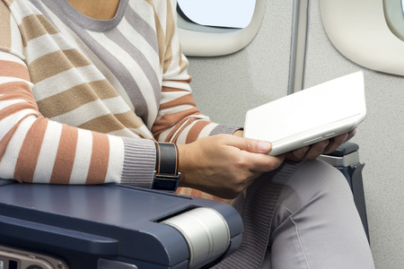 electronic tablet: caucasian woman passenger in airplane using  tablet smart device Stock Photo