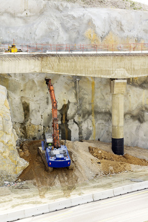 mine site: large jackhammer destroying on the highway slope in construction site and  excavator picks up large stones