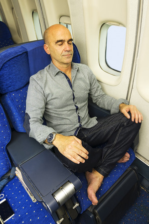jetsetter: caucasian man passenger  in airplane resting quietly in the seat Stock Photo