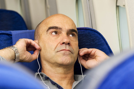 airplane girl: caucasian man passenger in airplane  resting in the seat  using mobile smart device with  headphones close up Stock Photo