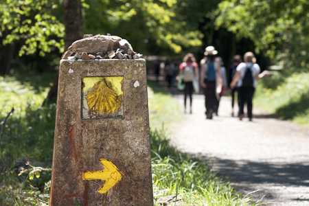 pilgrims  in Way of St James with sign shells marks to Compostela Cathedral ,Galicia, Spain