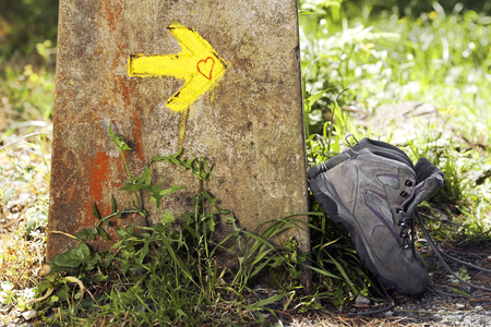 way of st james: pilgrim boots in Way of St James with yellow arrow mark  to Compostela Cathedral ,Galicia, Spain