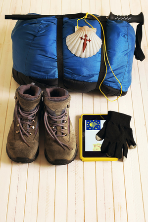 way of st  james: Pilgrim shell, boots, sleeping bag and tablet for Way of St James to Compostela Cathedral, Spain. Santiagos road Stock Photo
