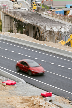 retrofit: car circulating in the highway while bulldozers destroying a bridge on the old road
