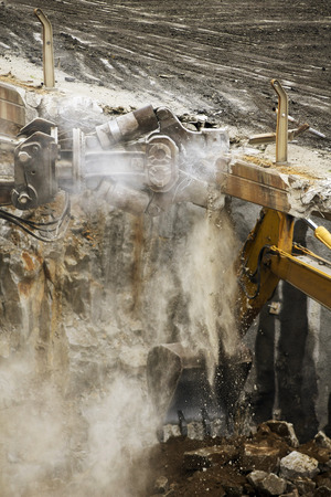 excavator demolition vehicle heavy equipment  tearing down  a bridge over the freeway in  aerial view close up Stock Photo