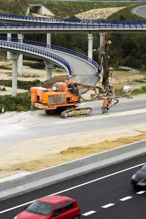 stabilizers: rock drilling caterpillar vehicle in highway construction site Stock Photo