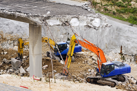 excavators vehicles heavy equipment pick rocks under demolished freeway bridge in aerial view