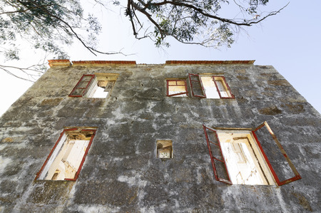mud house: facade of  old stone house  with wooden destroyed  windows