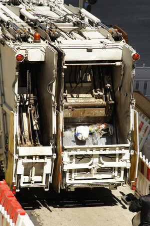 garbage collector: garbage collector truck vehicle  of utility municipal service company in  street   city Foto de archivo