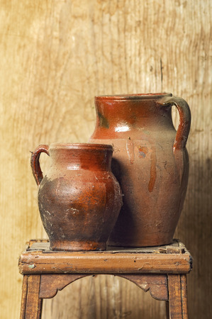 carves: antique mud pottery with wooden background