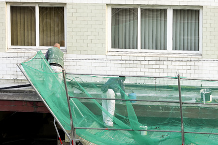 furnish: construction workers repairing and painting ledge building with protection on scaffolding