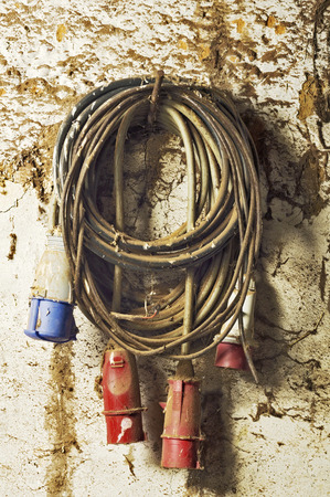 adobe wall: electric extension cord plug in the adobe wall Stock Photo