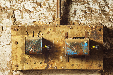 mud wall: antique electric industrial switches in  old mud  wall Stock Photo