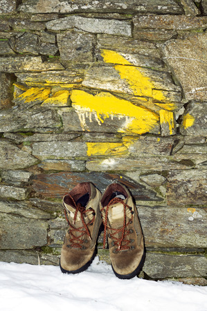 camino: Way of St James , Camino de Santiago, yellow arrow mark and pilgrim boots  to Compostela Cathedral ,Galicia, Spain