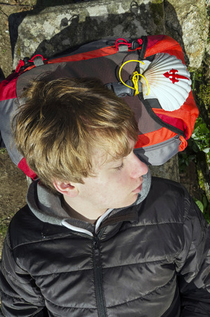way of st  james: young pilgrim resting with shell  in Way of St James,  Camino de  Santiago, to Compostela, Galicia, Spain