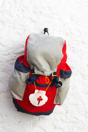 compostela: pilgrim scallop and backpack on whitewashed wall , Way of St James,  Camino de  Santiago, to Compostela, Galicia, Spain